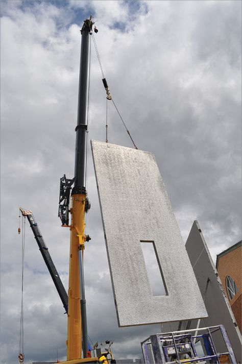 Pre-cast concrete panel being hoisted in place by crane